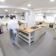 The bright, white kitchen is spacious and has a central island for demonstrations